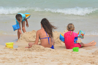 Familie mit Schulkindern am Strand